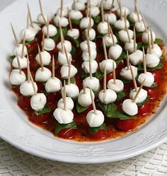 Chelsea's Caprese Canapé:  Italian dressing toothpicks mozzarella pearls fresh basil leaves torn into small bits grape tomatoes halved 1. Pour enough Italian dressing to cover the bottom of serving platter 2. Onto each toothpick stack one mozzarella pearl one piece of basil leaf and one half of a grape tomato with the sliced side facing down so the toothpick will stand up. 3. Place assembled hors d'oeuvres onto serving platter. From Mary Jane's Farm.