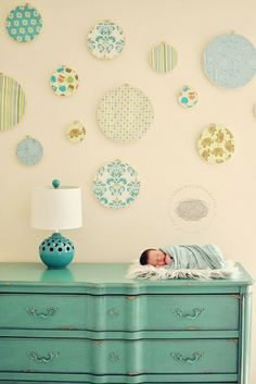 baby on changing table dresser with wall decorations above