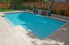 This swimming pool has been designed with a family in mind. Featuring two alcoves, a Sheer De. This swimming pool has been designed with a family in mind. Featuring two alcoves, a Sheer Descent Waterfall and frameless glass pool fencing, this swimming , Backyard Pool Landscaping, Small Backyard Pools, Swimming Pools Backyard, Swimming Pool Designs, Garden Pool, Backyard Ideas, Landscaping Ideas, Paving Ideas, Gunite Swimming Pool