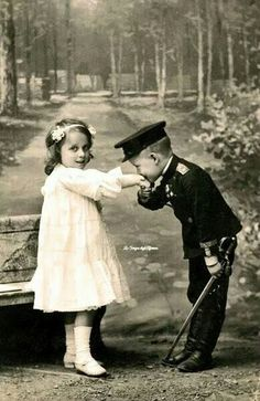 Young lad kissing a girls hand.