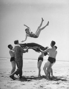 Army men bouncing starlet Marjorie Woodworth into the air. Photograph by John Florea. USA, 1942.bg