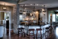 Beautiful #KitchenDesign with White Cabinets, Stainless Steel Appliances and Dark Wood Floors. The large island and seating area is perfect