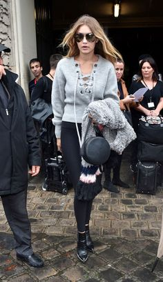 Gigi Hadid wears a lace-up sweater, leggings, boots, mirrored sunglasses, and a leather circle bag