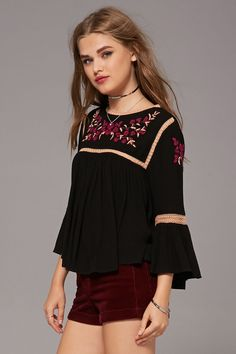 A crinkled peasant top featuring a floral embroidery, crochet lace cutout trim, round neckline, long bell sleeves, keyhole back, and a boxy silhouette.