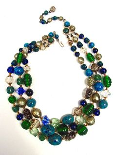 A Czech art glass in multi colors necklace with 3 strands....vintage: The necklace is rich in multi colors of art glass and has 3 strands. The art glass comes in various sizes, forms, colors and textures....all with fluted end caps and chain linked. Please view the photographs for