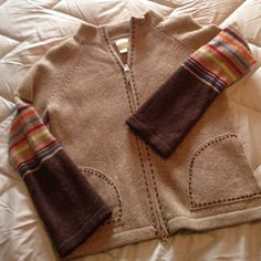 Garnet Hill zip front cardigan sweater size med. Ladies size medium Garnet Hill cardigan sweater in light brown with dark brown color blocking and multi striped sleves. Great details of contrasting stitching in pockets and down the front. Zips closed, 100% wool. Happy to bundle with other items to save you on shipping.  HAS very small darker drown stain on front which is barely noticeable ( see photo 3). Garnet Hill Sweaters Cardigans
