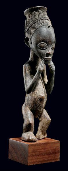 STATUETTE LUBA  République Démocratique du Congo  Statuette magico-religieuse d'un très bel et ancien style. Le crâne ovoïde est surmonté d'une coiffe ouvragée profondément évidée. Cette cavité contenait très certainement une charge magique, aujourd'hui disparue. Les deux mains se joignent au niveau du menton mettant ainsi en avant l'expression d'effroi du personnage. Hauteur: 26 cm