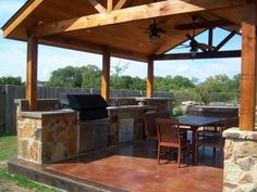 Here's a beautiful stamped concrete patio gable roof built on top of stone pillars.