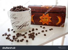 White coffee mug and beans. Wooden box in background. #coffee #shutterstock #stockphoto #mug