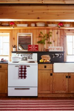 Pops of red are found in peppy doses throughout this Christmas cabin's kitchen. From the task clip-on lighting shown here to the vintage lanterns lining the living room mantel. Candy cane-striped runners (there's also one in the entry) offer a sweet nod to the classic Christmas treat without going too theme-y .Metal finds add instant patina to the newly updated kitchen.