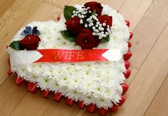 Large heart funeral tribute.  White chrysanthemum, large roses, gypsy grass, diamonties, black butterfly and red white ribbon with the word wife.