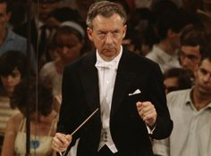 English composer Benjamin Britten conducting at the podium.