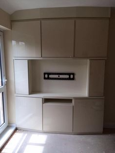 TV/media unit Fitted media unit with space for flat screen TV in a high gloss cream and curved to suit this apartment
