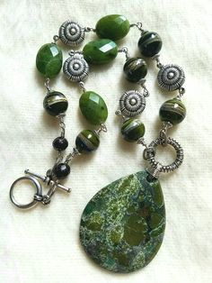 My hoarded bead (or in this case pendant). A green gorgeous goodie that rocks! Literally. Look at all those different shades of green. Green means spring. And spring means new life. I pulled out faceted jade I've had for awhile to represent the new buds of life emerging from winter's slumber. Then I pulled out the oxidized sterling silver plated brass connectors whose circles symbolize Mother Earth. Something was m Trendy Jewelry, Jewelry Trends, Meditation Crystals, Different Shades Of Green, Oxidized Sterling Silver, Mother Earth, Crystal Healing, Pendant Necklace, Gemstones