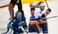Andrew Ladd's goal gives Islanders OT win over Canucks  -  March 10, 2017:  Vancouver Canucks goalie Ryan Miller waits as New York Islanders left wing Andrew Ladd (16) celebrates his goal with teammate Calvin de Haan (44) during overtime in an NHL hockey game Thursday, March 9, 2017, in Vancouver, British Columbia. Photo Credit: Jonathan Hayward / The Canadian Press via AP