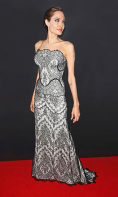 On the red carpet, Angelina Jolie sticks to what works.  If she's not borrowing from the boys and wearing a well-tailored tuxedo, the actress usually opts for a dress with a tight-fitted bodice that shows off her figure in a neutral color.  The 39-year-old didn't stray from her somewhat predictable signature style at the Australian premiere of her new film, Unbroken. Wearing a lace gown by GUCCI Première, the fashion house's haute couture collection, Jolie, who directed the movie, which is…