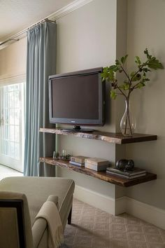 Fantastic bedroom features a chaise lounge facing stacked live edge wall shelves lined with a flatscreen TV.