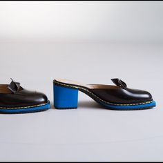"""OMG Made in Italty Mules by Viktor & Rolf The ultimate in indulgent lux footwear, these V&R loafer/mules are outrageously gorgeous.  Made in Italy quality luminous black leather, and chic origami detail are given edge by the blue heel and sole, then offset by the yellow stitching.  Everyone will be envious!  These run very narrow!  Marked M by fit like N.  Approx 2 1/2"""" heel, 1/2"""" platform.  Like new with almost no sign of wear inside or out! VIKTOR & ROLF Shoes Mules & Clogs"""