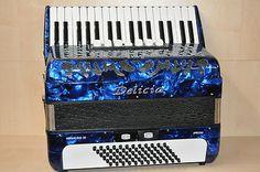 """NEU         Delicia    Arnaldo 23    blau         Diskant: 34 Tasten, 7 Register, 3-chörig    Bass: 72 Bass, 2 Register    Farbe: blau    """"Tipo a mano"""" - Stimmplatten    Inkl. Tragriemen und Koffer"""