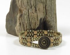 An adorable hand beaded bracelet utilizing opaque ultra luster green SuperDuos, bronze SuperDuos, bronze Czechmate Tiles, and opaque luster transparent greenToho seed beads. The tiles are woven side by side and alternate with a SuperDuo design to make a very stylish bracelet. The clasp is a TierraCast antique bronze button in an Aztec design with a SuperDuo loop that slides over the top.  When the bracelet is clasped it measures 7 around and is 1/2 wide…