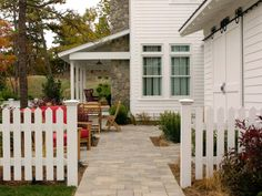 A stylish paver walkway leads to a comfortable sitting area, outdoor dining table and covered porch all enclosed in a charming, white picket fence.