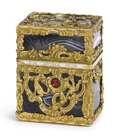 "A GEORGE III GOLD AND AGATE NECESSAIRE, CIRCA 1760 rectangular, the striated translucent grey agate sides overlaid with gold cagework chased with flowers and scrolls including a cockerel, hound, exotic bird and squirrel, the cover rim inscribed on white enamel ground ""DOVE REGNA LA STIMA NON CANGIA AMORE"", ruby thumbpiece, fitted with the following gold-mounted items: ivory writing slide, two scent bottles, folding knife, spoon, pencil, tweezers"