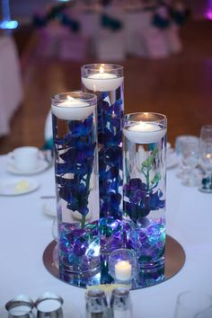 These are the center pieces from my peacock wedding. Used once and then packed away, so in very good condition. The beautiful silk blue violet orchid stems are all pre-cut to fit inside the vases. All you need to get are the floating candles and the submersible lights. I am including the table stands because …