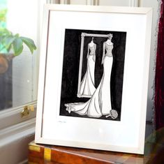 """The customer was SO happy she rang me to say """"Thank you."""" Don't you love that?  This is a 20 year anniversary gift. The fashion illustration captures the wedding dress, bouquet and shoes 20 years after the wedding day.  A Mirror View Ink Painting.  #WeddingDressInk #GiftGuide  #WeddingGiftVoucher #BestWeddingGiftEver #bestweddingpresentever #firstanniversarygift #anniversarygift #weddinggiftideas #weddinggift #luxuryweddinggift #weddingdressportrait Wedding Dress Drawings, Wedding Dress Illustrations, Fashion Illustration Dresses, 20 Year Anniversary Gifts, Custom Wedding Dress, Wedding Dresses, Luxury Wedding Gifts, Custom Mirrors, Black Gift Boxes"""