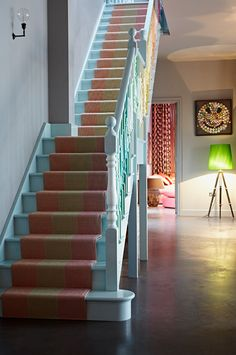 Eclectic Staircase - runner colours pick up just seen sitting room beyond. Love the blue steps - not sure about the multicoloured railing. Muted grey walls keep colours under control. Love the wall light.