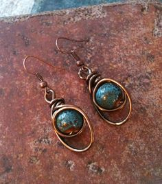 Copper wire wrapped earrings with blue speckled ceramic beads and copper earring wire.  1 1/4 in length from base of earring wire.