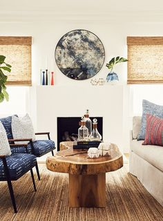 Living room with a fireplace, a rustic mirror, a raw wood coffee table and printed midcentury modern armchairs