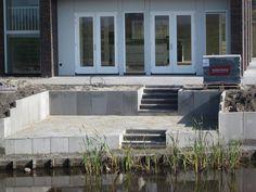 Terras aan de waterkant met betonnen keerwanden en trappen. Particulier nieuwbouw project.