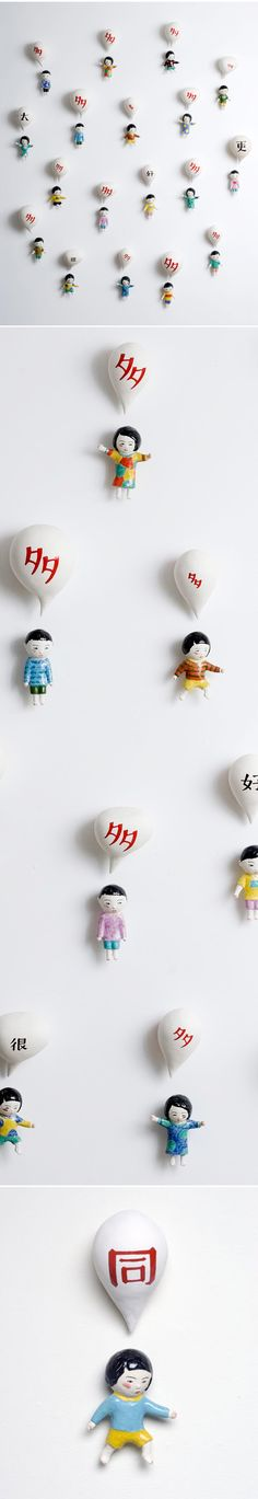 "Ceramic children stuck to the wall. by American artist Beth Lo – she was born in the USA to parents who had immigrated from China…      ""My work revolves primarily around issues of family and my Asian-American background. Cultural marginality and blending, tradition and Westernization, language and translation are key elements in my work.""  Beth is a professor of ceramics & drawing at the University of Montana"