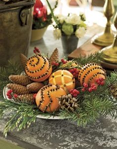 Pomander Display:   Make this fragrant holiday arrangement with pomanders, pinecones, and holiday greens displayed on a transferware plate. Score patterns on the oranges with a citrus striper or channel knife, make pilot holes with a small nail, then stud the oranges with whole cloves.   Photo Credit: Steven Randazzo
