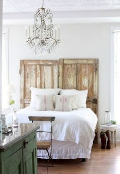 Distressed old doors as headboards.  Add a silver-blue whitewash to add color to a white room.