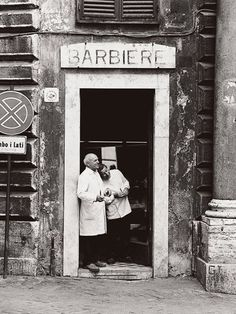 Two barbers await their next customer in the doorway of one of Rome's oldest barbershops.  PHOTOGRAPH BY KEN KOCHEY