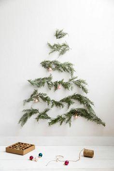 immergrüne Zweige an der Wand befestigen und dekorieren