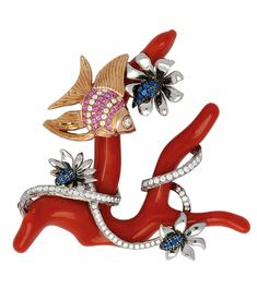 A Coral, Diamond and Sapphire Brooch The coral branch decorated with an angelfish amid flowers and coiling ribbons, accented with round diamonds, pink and blue sapphires, mounted in platinum and 18k gold