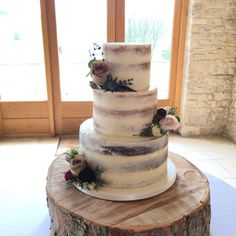 Semi naked cake with fresh flowers at Kingscote Barn, Tetbury, Gloucestershire.