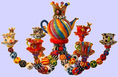 Tea-set Chandelier - Ceramics by Mary Rose Young, England - The central wiring is all covered up under a magnificent ceramic teapot, while the bulb holders are 6 cups & saucers. The metal frame is cloaked with hand made multi coloured ceramic beads.