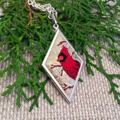 This is so festive and sweet! A tiny red Cardinal, snowy branches and falling snow have been hand embroidered on a shimmery gold metallic wool blend felt, set in a silver pendant.    https://www.etsy.com/listing/255351020/cardinal-necklace-embroidery-jewelry