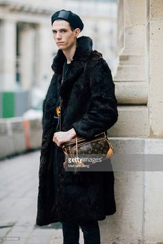 Model/Designer Marc Sebastian Faiella wears a black Louis Vuitton beret, large black fur coat, and a Louis Vuitton monochrome leather side pack bag after the Paul Smith show at Bourse du Commerce on Day 5 of Paris Fashion Week Mens on January 24, 2016 in Paris, France.