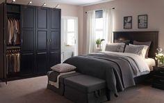 Iso makuuhuone, jossa musta sänky ja mustat yöpöydät sekä musta vaatekaappi ja kaksi harmaalla kankaalla verhoiltua rahia.