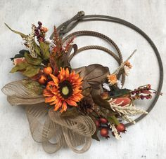 This beautiful autumn lasso wreath is rustic farmhouse with a contemporary feel to this design. Lasso is Authentic and flowers are artificial for use year after year. Approximately 2 feet in diameter Burlap bow completes this arrangement Rope Crafts, Fall Crafts, Holiday Crafts, Fall Wreaths, Door Wreaths, Antler Wreath, Barbed Wire Wreath, Western Wreaths, Horse Head Wreath
