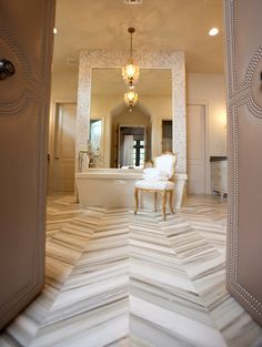 Elegant Master Bathroom - LOVE - double doors trimmed with silver nail heads and stunning marble floor finished in a chevron pattern
