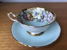 Vintage Paragon Teacup and Saucer This is a spectacular wide teacup and saucer in a light blue colour, sometimes it looks like a blue-aqua in certain light. This set has orange, yellow, purple and pink poppies or anemones with green leaves. This set has a heavy gold border, gold accents on