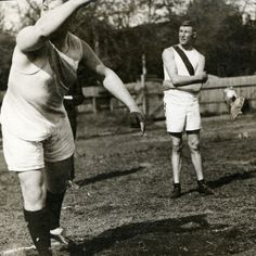 Black and white photo of University of Oregon athlete Bob Kellogg as he watches another, unidentified athlete, release either a discus, or shot, at Kincaid Field in 1910. ©University of Oregon Libraries - Special Collections and University Archives