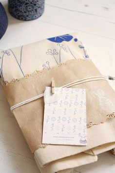 Inspiration - Craft punched edges of kraft wrap + white twine + miniature clothespin. Pefect wrap for something like a tote bag, dishtowels, etc...