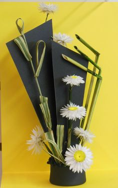 """""""Cabaret"""" by Jan Krass is an 8"""" small panel design using paper daisies, striped ribbon grass, and commercially-purchased equisetum.  Broom corn, painted black, forms the tiny """"beads"""" that cover the foam in the container (milk bottle lid).  The panels are made of textured cardstock with toothpick """"legs.""""  Blue ribbon. 2015 Clay Co. Fair"""