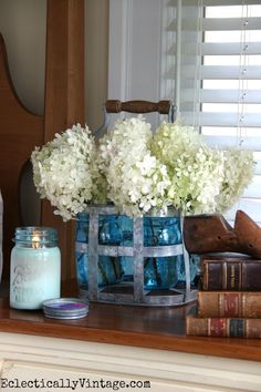 Don't neglect your bedside table - display favorite things like an amazingly scented candle, vintage books and a galvanized bottle carrier from HomeGoods used as a vase for a huge bouquet of hydrangeas.  See more of this stunning bedroom eclecticallyvintage.com sponsored pin
